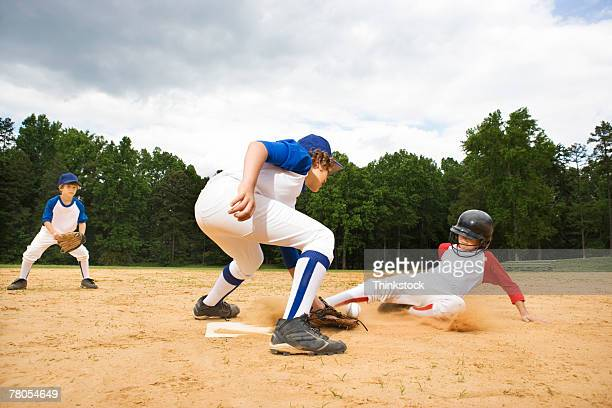 Young runner sliding into base