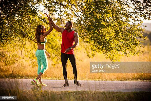 Young running couple giving high fives in park