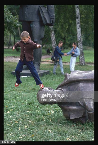 A young Russian boy jumps off the head of a toppled Stalin statue placed in a 'cemetary' following the failed coup attempt
