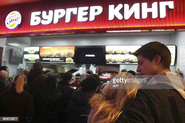 A young Russian couple hugs while waiting in line on the opening day at Russia's first Burger King fast food restaurant in Moscow on January 21 2010...