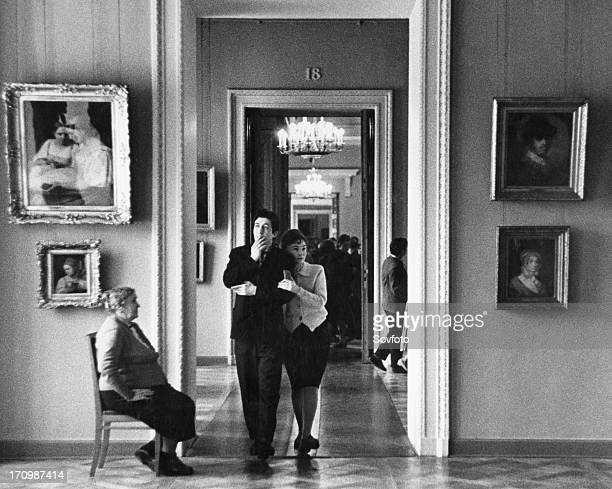 A young russian couple walk through the halls of a moscow museum art gallery ussr 1960s