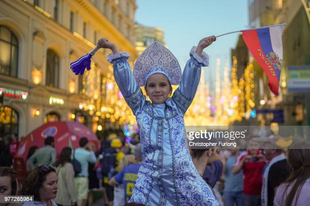 A young Russian girl joins World Cup football fans as they enjoy the party atmosphere on Nikolskaya Street near Red Square on June 17 2018 in Moscow...