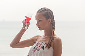 young russian woman drinking champagne seaside