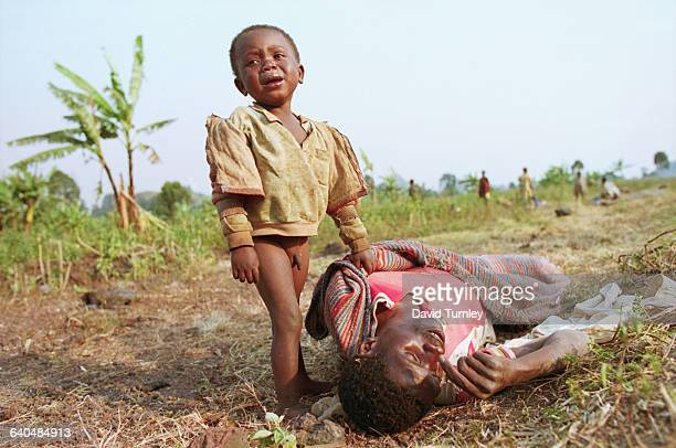 A young Rwandan boy cries and clings to his dead father who died moments before of cholera The two had fled the HutuTutsi violence in Rwanda and come...