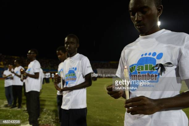 Young Rwandan men hold candles during a night vigil and prayer for genocide victims at the Amahoro stadium in Kigali Rwanda on April 7 2014 Solemn...