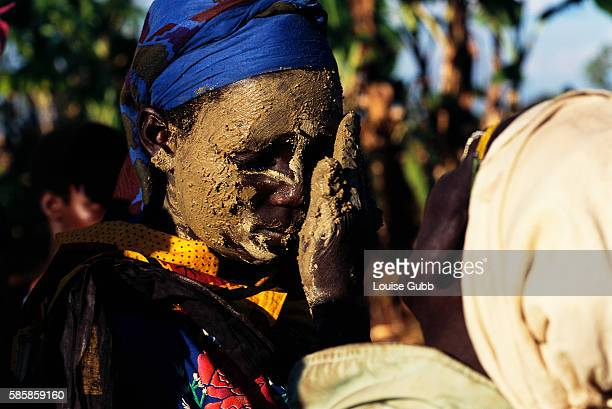 A young Sabiny girl prepares for a circumcision ceremony by having her face painted with mud by an elderly caregiver While a traditional rite of...