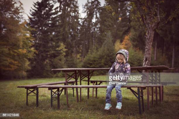young, sad child sitting alone at an outdoor picnic table - ausschluss stock-fotos und bilder