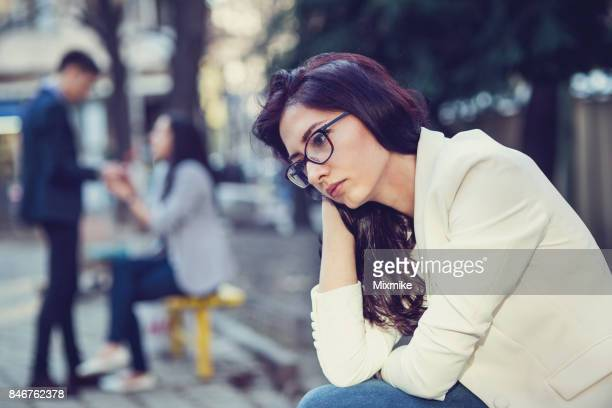Young sad female sitting in the park