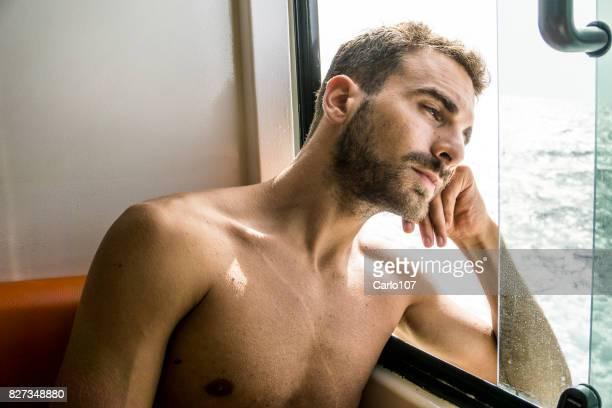 Blick aus dem Fenster auf einer Fähre traurig Jüngling