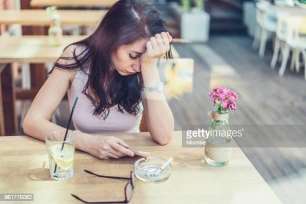 彼女の携帯電話を手に、カフェに座って若い悲しい女性