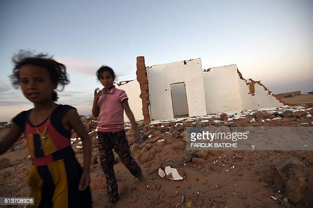Young Sahrawi refugees stand next to a house which was destroyed during heavy rain last year at the Boujdour refugee camp near the Algerian city of...