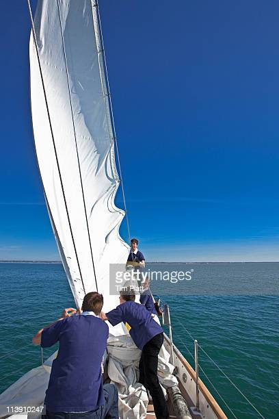 A young sailing crew  work as a team.