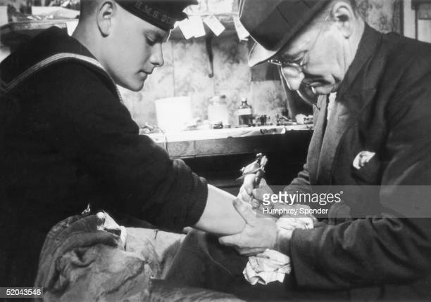 Young sailor in the British navy gets a tattoo on his arm in a Portsmouth tattoo parlour, 19th August 1939. Original Publication : Picture Post - 202...