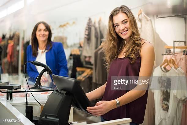 Junge Verkäufer und Chef lächelnd in die Kamera.
