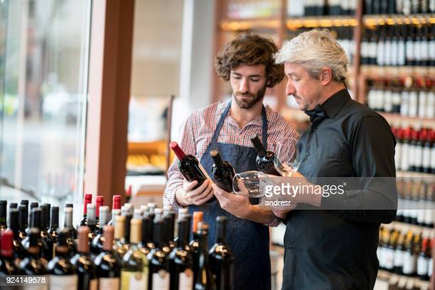 young sales clerk and business owner looking at bottles of wine while owner holds wine glasses at a winery - liquor store stock pictures, royalty-free photos & images