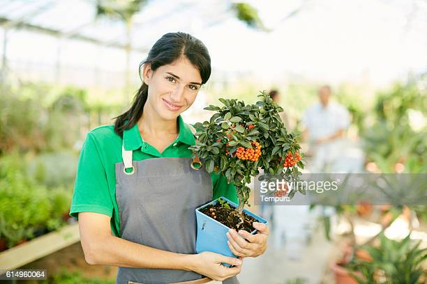 Young sales clerk looking at camera in a Garden Center