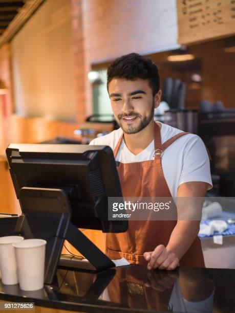 ung kontorist arbetar på ett bageri som lägger order på systemet ser glad - voter registration bildbanksfoton och bilder