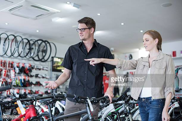 Young salesman and client looking at bicycles