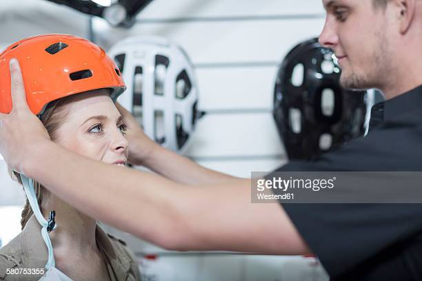 Young salesman putting bicycle helmet on womans head