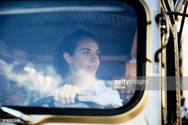 young saleswoman looking away while driving food truck - camioneros fotografías e imágenes de stock