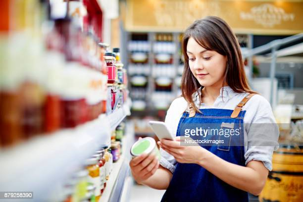 Young saleswoman scanning label on food container with smart phone