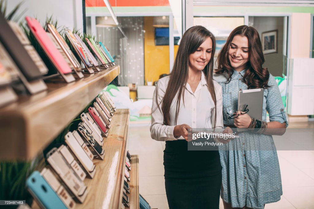 Young saleswoman showing brochure to female customer at electronics store : Stock Photo