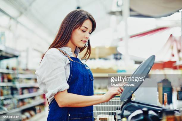 young saleswoman using cash register in delicatessen - convenience store counter stock photos and pictures