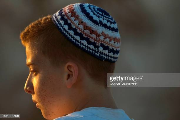 A young Samaritan worshiper prays on top of Mount Gerizim near the northern West Bank city of Nablus as they celebrate the Shavuot festival at dawn...
