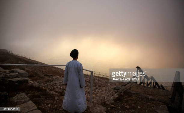 TOPSHOT A young Samaritan worshiper walks at dawn on top of Mount Gerizim near the northern West Bank city of Nablus on June 24 2018 during...