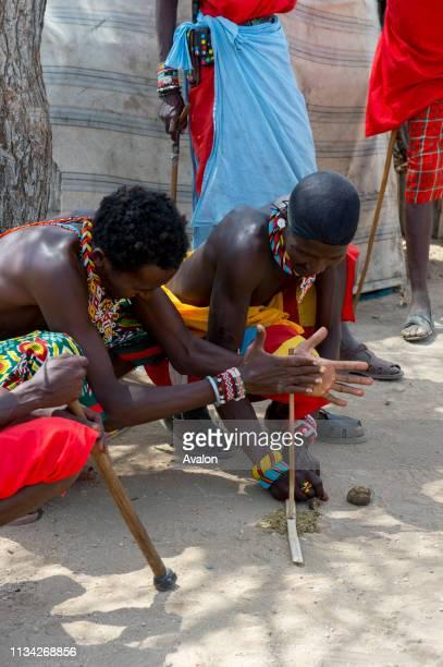 Young Samburu warriors demonstrating how to start a fire with sticks in a Samburu village near Samburu National Reserve in Kenya