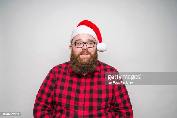 young santa claus wearing a plaid shirt - santa hat stock photos and pictures