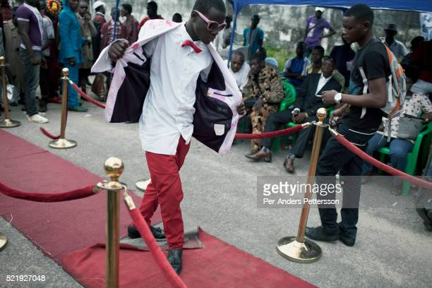 A young Sapeur parades and shows his designer label clothes including Versace while paying their respect to Stervos Nyarcos the founder of the...