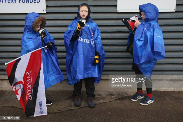 Young Saracens supporters take shelter from the rain prior to the European Rugby Champions Cup match between Saracens and Northampton Saints at...