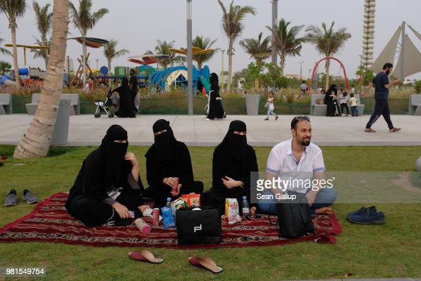 Young Saudis including three women wearing the traditional niqab and black abayas relax on the Corniche waterfront on June 22 2018 in Jeddah Saudi...