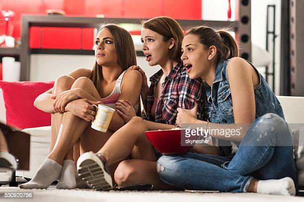Giovani donne guardando film horror paura a casa.