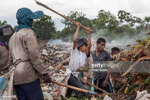 A young scavenger boy digs with a pickaxe between tons of trash in the Anlong Pi landfill on June 11 2014 in Siem Reap Cambodia Dozens of children...
