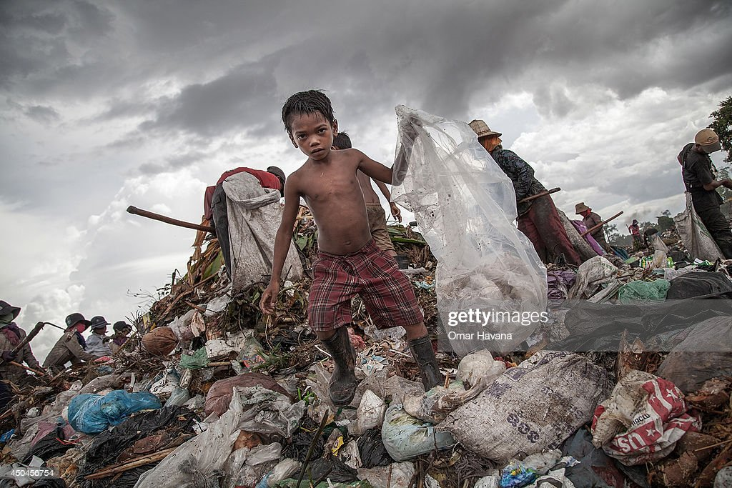 A young scavenger boy grabs plastic between tons of trash in the Anlong Pi on June 11, 2014 in Siem Reap, Cambodia. Dozens of children work every day in the Anlong Pi landfill, which is situated only few kilometres aways from the world famous Angkor temples, visited by more than 3 million tourists every year. Despite the Cambodian government's commitments and legal responsibilities to end child labor - enshrined in its ratification of relevant international covenants, domestic laws and the implementation of several national policies aimed at ending child labor - it remains a significant concern in Cambodia, where almost a third of the population lives on less than a dollar per day. Child labor is a consequence of this poverty, often resulting from a family's inability to support itself. According to a recent report from the International Labour Organisation (ILO), an estimated 19.1% of the close to 4 million children in Cambodia between the ages of 5 and 17 engage in economic activities. An estimated 56.9% of those children are child labourers, with a third of them being involved in hazardous activities mostly in the agriculture, forestry and fishing sectors.