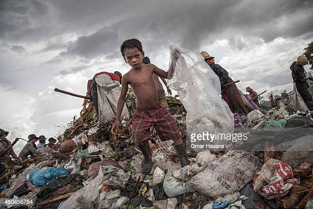 A young scavenger boy grabs plastic between tons of trash in the Anlong Pi on June 11 2014 in Siem Reap Cambodia Dozens of children work every day in...