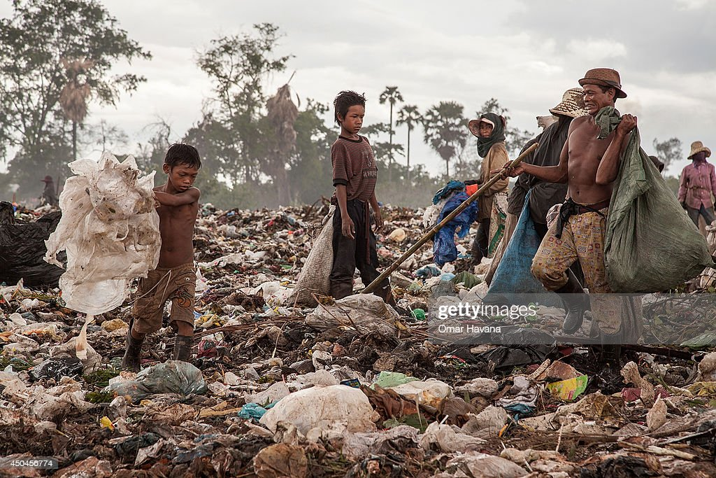 A young scavenger boy grabs plastic between tons of trash in the Anlong Pi landfill on June 11, 2014 in Siem Reap, Cambodia. Dozens of children work every day in the Anlong Pi landfill, which is situated only few kilometres aways from the world famous Angkor temples, visited by more than 3 million tourists every year. Despite the Cambodian government's commitments and legal responsibilities to end child labor - enshrined in its ratification of relevant international covenants, domestic laws and the implementation of several national policies aimed at ending child labor - it remains a significant concern in Cambodia, where almost a third of the population lives on less than a dollar per day. Child labor is a consequence of this poverty, often resulting from a family's inability to support itself. According to a recent report from the International Labour Organisation (ILO), an estimated 19.1% of the close to 4 million children in Cambodia between the ages of 5 and 17 engage in economic activities. An estimated 56.9% of those children are child labourers, with a third of them being involved in hazardous activities mostly in the agriculture, forestry and fishing sectors.