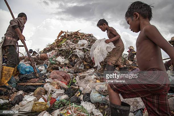 A young scavenger boy grabs plastic between tons of trash in the Anlong Pi landfill on June 11 2014 in Siem Reap Cambodia Dozens of children work...