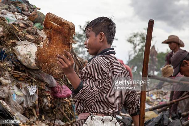 A young scavenger boy holds a piece of rotten metal that he found while working between tons of trash in the Anlong Pi landfill on June 11 2014 in...