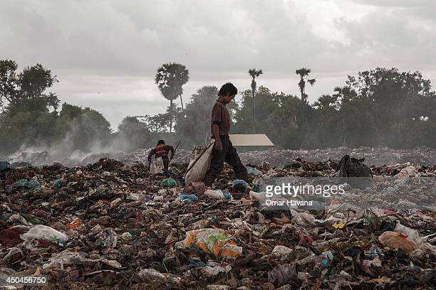 A young scavenger boy search for recyclable material between tons of trash in the Anlong Pi landfill on June 11 2014 in Siem Reap Cambodia Dozens of...