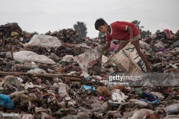 A young scavenger boy searches for recyclable material between tons of trash in the Anlong Pi landfill on June 11 2014 in Siem Reap Cambodia Dozens...