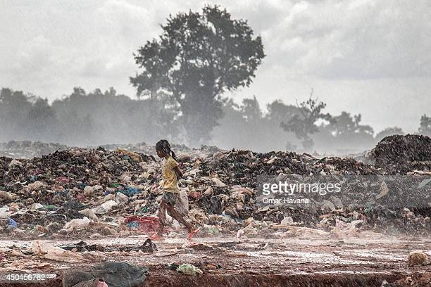 A young scavenger girl runs to her shelter after a storm breaks over the burning pile of trash in the Anlong Pi landfill on June 11 2014 in Siem Reap...