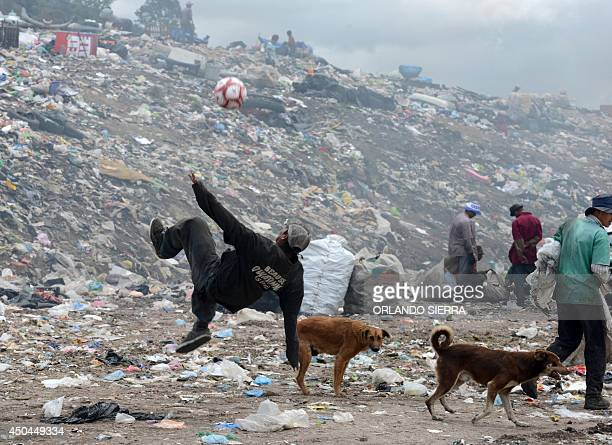 A young scavenger plays with a football in the municipal incinerator grounds in the outskirts of Tegucigalpa on June 11 2014 AFP PHOTO/Orlando SIERRA