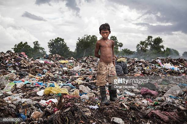 A young scavenger poses over tons of rubbish where he searches everyday for recyclable material that he sells to make a living in the Anlong Pi...
