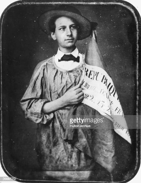 A young scholar of the French revolution of 1848 bearing a banner with the revolutionary ideals 'Liberte Egalite Fraternite' emblazoned on it