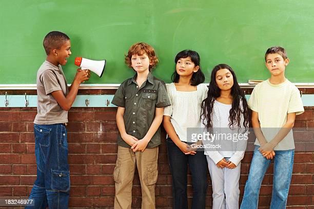 École jeune garçon crier à ses amis à l'aide de porte-voix