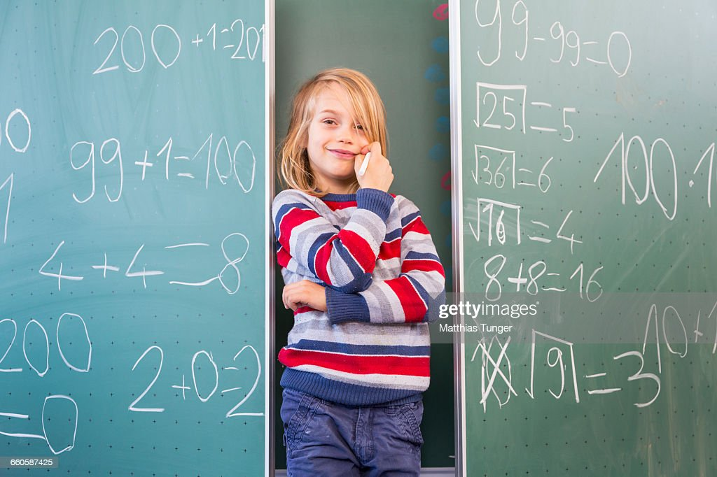 young school boy standing in front of a blackboard : Stockfoto