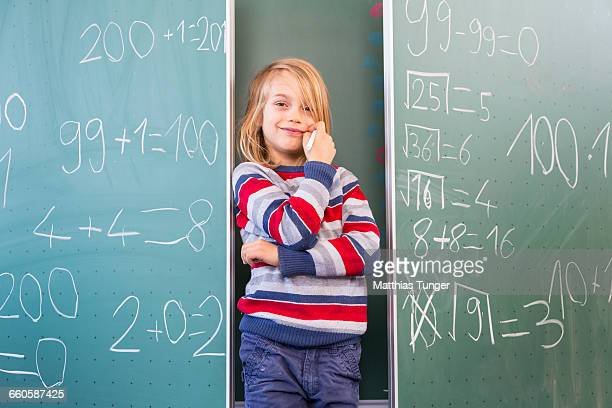 young school boy standing in front of a blackboard - schulkind stock-fotos und bilder